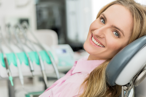 blonde woman in a dental chair thinking about her upcoming full mouth reconstructive surgery in Tallahassee, FL
